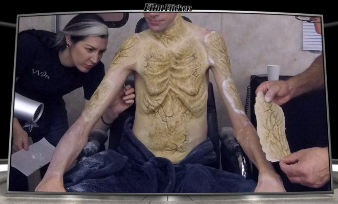 Image of an actor getting prosthetics makeup attached to his body