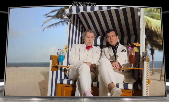 Image of Gary Oldson and Antonio Banderas sitting in a hut on the beach