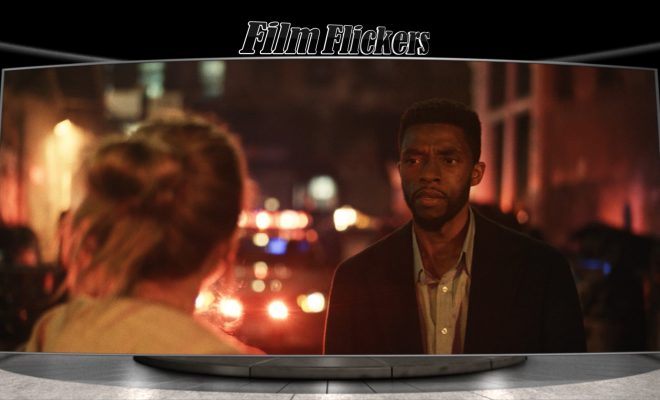 Image of Chadwick Boseman as a detective in 21 Bridges talking to a female