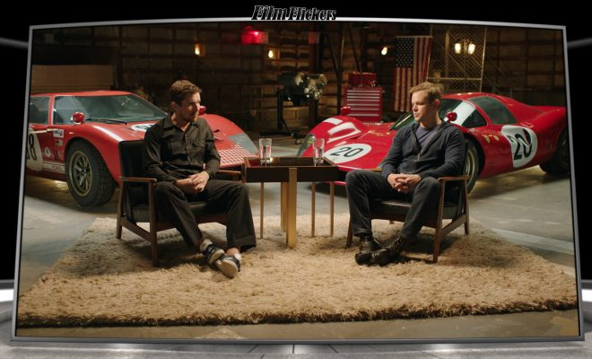 Image of Christian Bale and Matt Damon on an interview set with both a Ferrari and a Ford race cars behind them