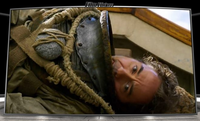 Image of Robert Downey Jr as Dolitle laying down on side on boat in sub suit looking towards an animal