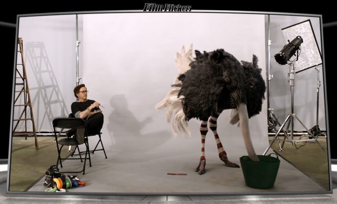 Image of Robert Downey Jr. sitting on a chair next to an ostrich with it's head inside a bucket