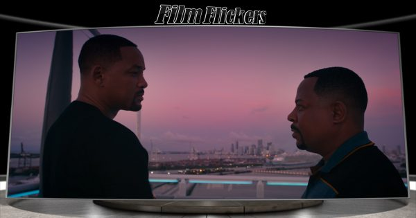 """Image of Will Smith and Martin Lawrence looking at each other with a city skyline behind them in """"Bad Boys For Life"""" movie"""