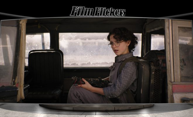 """Image of kid sitting inside old Ghostbusters car in """"Ghostbusters: Afterlife"""" film"""