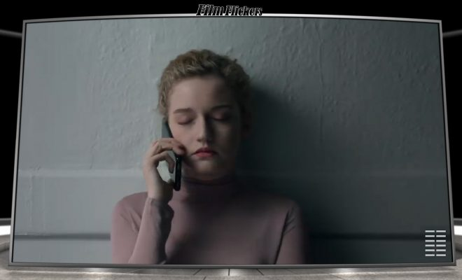 Medium shot of Julia Garner talking on her phone in the hallway