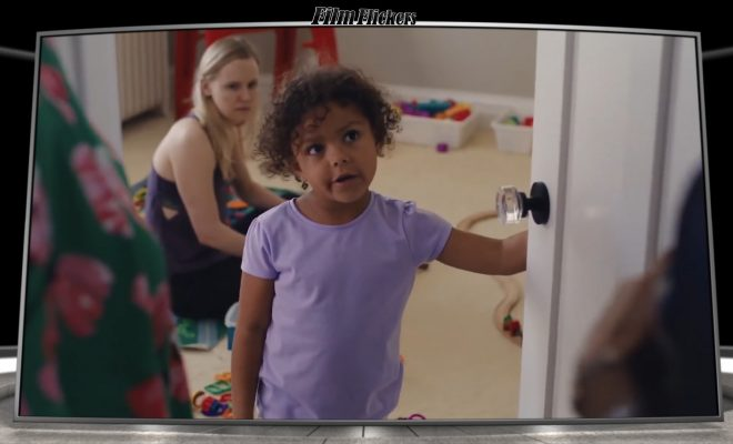 Image of a little girl holding door open to her bedroom talking to her parents while her babysitter is on the floor playing with the toys behind her