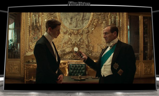 Ralph Fiennes handing Harris Dickinson a pistol in one of the Duke's rooms