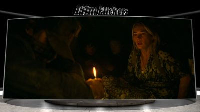 """Image of Emily Blunt in the film """"A Quiet Place Part II"""" off-centered in the dark while Cillian Murphy on the other side holding a candle"""