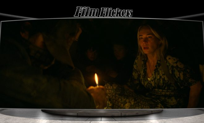 "Image of Emily Blunt in the film ""A Quiet Place Part II"" off-centered in the dark while Cillian Murphy on the other side holding a candle"