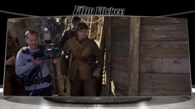 """Image of a 'behind the scenes' look of the film """"1917"""" showing soldier running in the trenches while camera operator capturing from the left side"""