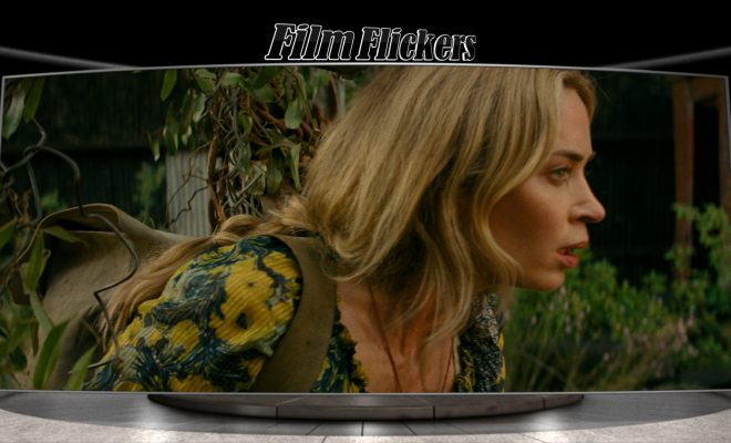 """Image of Emily Blunt walking quietly through the broken fence in """"A Quiet Place Part II"""""""