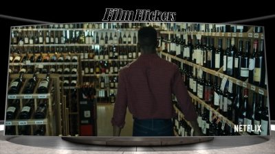 """Image of a man walking in a wine store, which is a scene from """"Uncorked"""""""