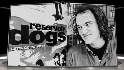 """Image of Quentin Tarantino looking at movie poster """"Reservoir Dogs"""", which is a scene from the documentary """"QT8: The First Eight"""""""