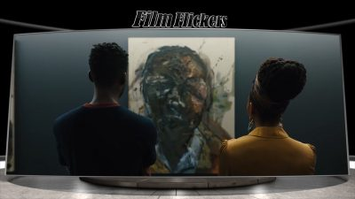 """Image of two people looking at a painting, which is a scene from the rebooted """"Candyman"""""""