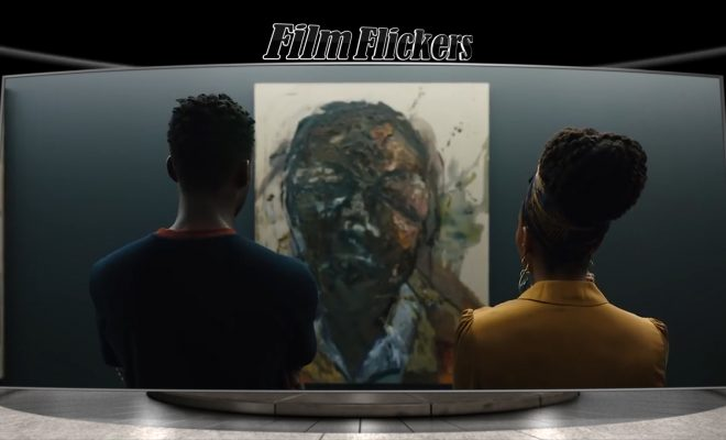 "Image of two people looking at a painting, which is a scene from the rebooted ""Candyman"""