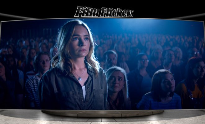 Britt Robertson stands up in the middle of the crowd with a spotlight.