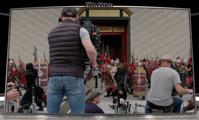 """Image of a behind-the-scenes look with a camera man shooting the battle scene from the film """"Mulan"""""""