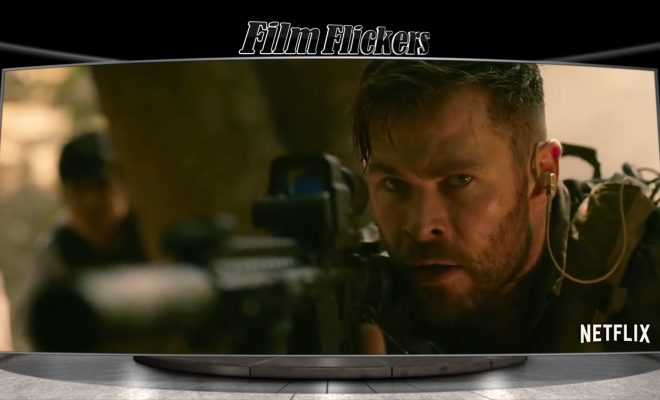 "Image of a scene from the film ""Extraction"" showing Chris Hemsworth holding a gun staying guard while crouching low to escape"