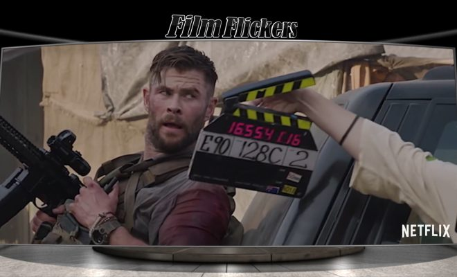 "Image of a behind the scenes look at the film ""Extraction"" showing Chris Hemsworth leaning on a car with a gun in hand and a movie marker showing cut to scene"