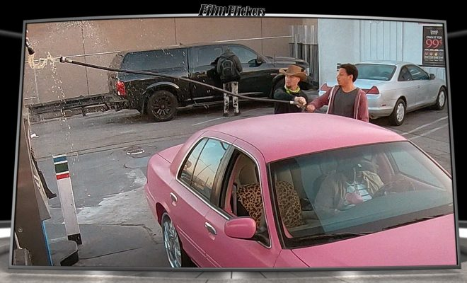 Image of Eric Andre pulling a gas line out of the station with a civilian near a pink car at a gas station