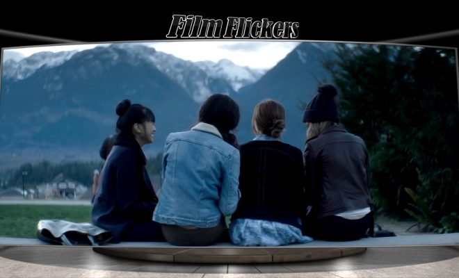 Image of four girls sitting on a log near a lake by a mountain in front of them