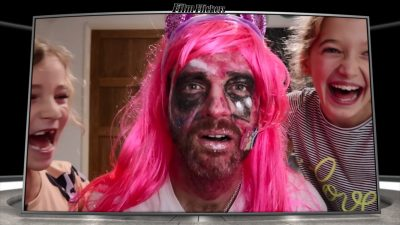 Image of a dad with heavy make-up and a pink wig, while his daughters on on each side of him laughing