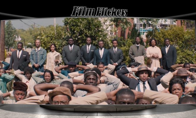 "Image of African-American folks down on their knees in the street with a group of other African-American folks standing behind them ready to protest peacefully back in the film ""Selma"""