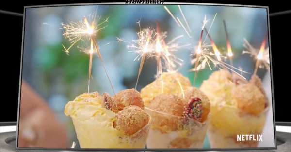 Image of a dessert with ice cream, doughnut holes with sparklers lit on top