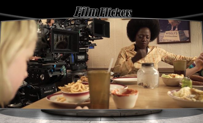 Image of a behind-the-scenes look with Viola Davis on set with Mckenna at a table about to eat with a camera to her side