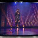 Image of Yvonne Orji doing stand up comedy on a purple-lit stage